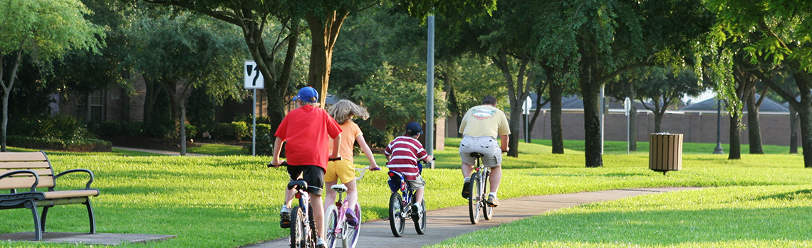 Family riding bicycles together down a trail